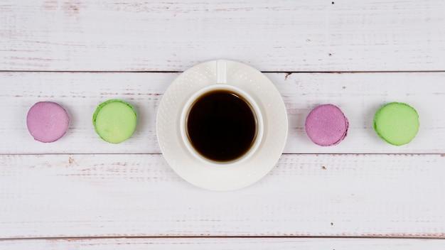 Kleurrijke bitterkoekjes en een kopje koffie op houten