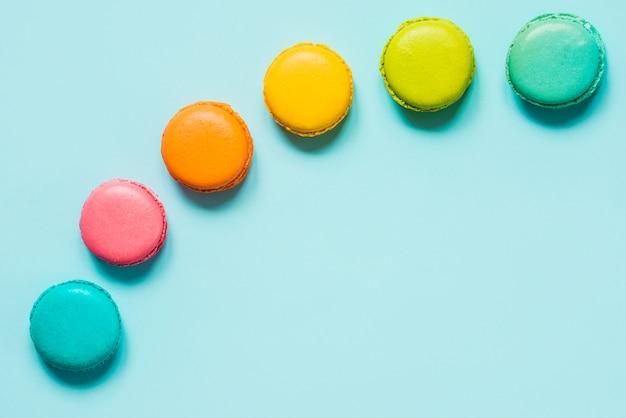 Kleurrijke bitterkoekjes gerangschikt als regenboog op blauwe achtergrond.