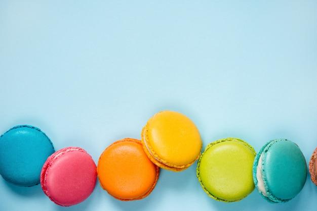 Kleurrijke bitterkoekjes gerangschikt op blauwe achtergrond. kopieer ruimte.