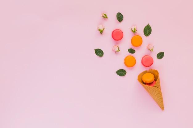 Kleurrijke bitterkoekjes; roos; en bladeren gerangschikt over de wafelkegel tegen roze achtergrond