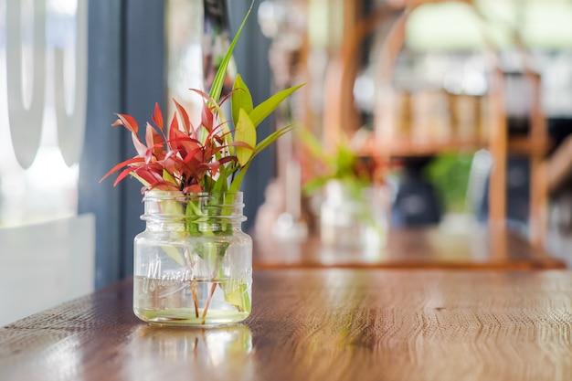 Kleurrijke bladtakken op een glaskruik die op een lijst in een restaurant wordt geplaatst