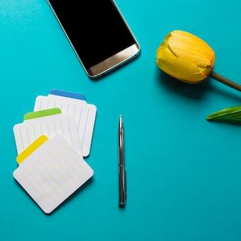 Kleurrijke blocnotes met pen; mobiele telefoon en gele tulpen op blauwe achtergrond