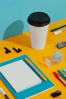 Kleurrijke blocnotes, pennen en papieren beker op oranje tafel