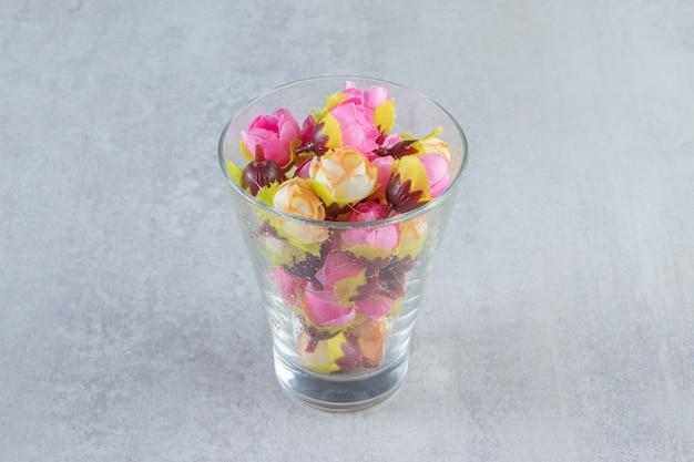 Kleurrijke bloem en glas, op de witte tafel.