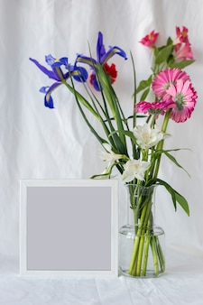 Kleurrijke bloemen in bloemenvaas met leeg fotokader op wit gordijn