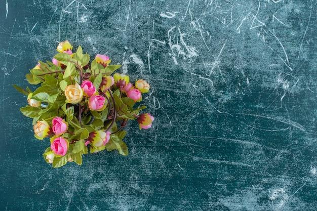 Kleurrijke bloemen in een houten kruik, op de blauwe achtergrond.