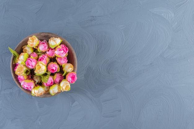 Kleurrijke bloemen in een kom, op de witte tafel.