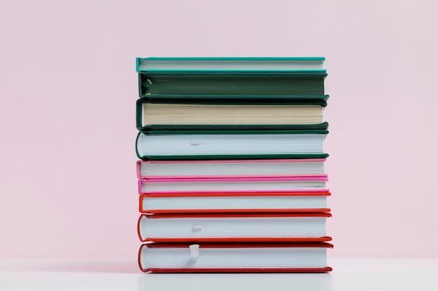 Kleurrijke boeken met roze achtergrond