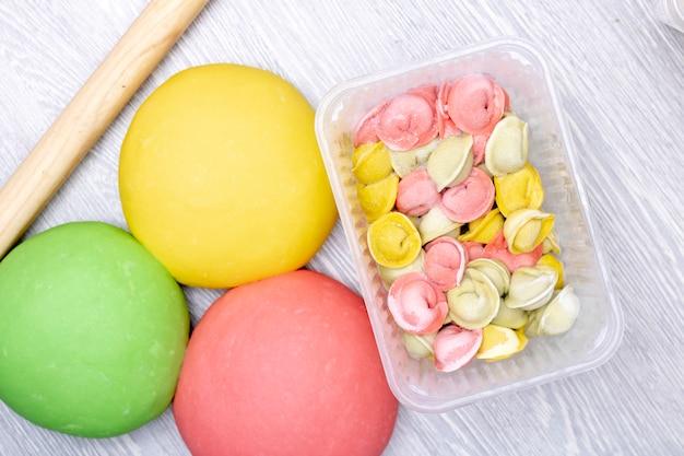 Kleurrijke bollen, pelmeni van rood, groen en geel deeg in container