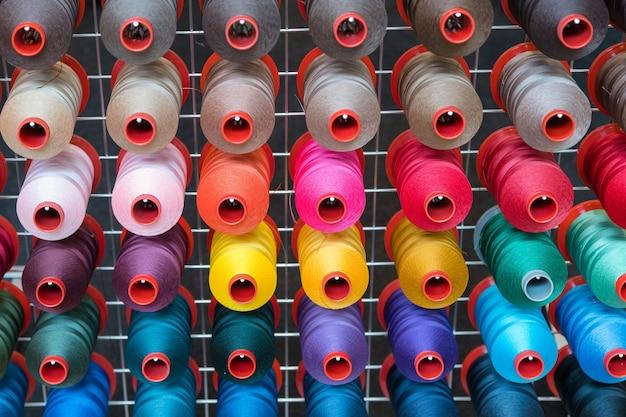 Kleurrijke borduurgarenklos die in de kledingindustrie wordt gebruikt, rij veelkleurige garenrollen, naaimateriaal dat op de markt wordt verkocht Premium Foto