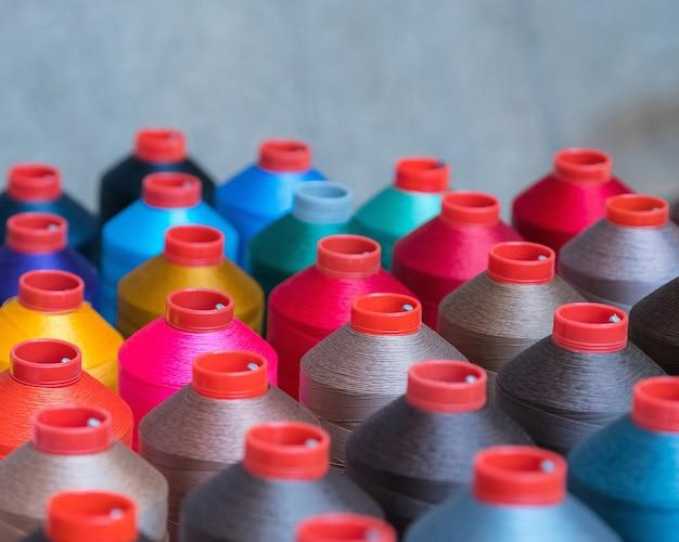 Kleurrijke borduurgarenspoel die wordt gebruikt in de kledingindustrie, rij veelkleurige garenrollen, naaimateriaal dat op de markt wordt verkocht