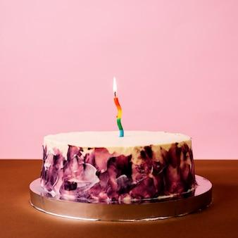 Kleurrijke brandende kaars op ronde cake over bureau tegen roze achtergrond