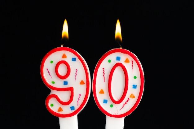 Kleurrijke brandende verjaardagskaars op dark