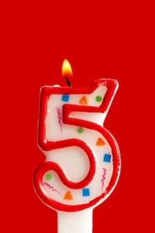 Kleurrijke brandende verjaardagskaars op rode achtergrond