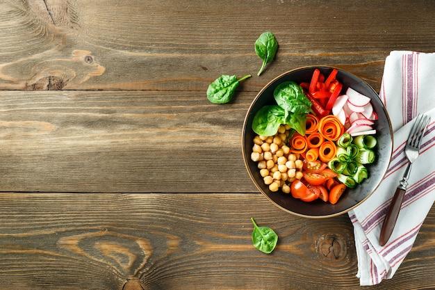 Kleurrijke buddha bowl met kikkererwten, wortelen, tomaten, komkommers, radijs en paprika op houten tafel. vegetarische salade. bovenaanzicht. kopieer ruimte.