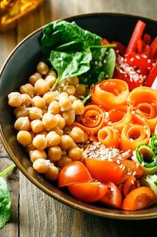 Kleurrijke buddha bowl met kikkererwten, wortelen, tomaten, komkommers, radijs en paprika op houten tafel. vegetarische salade.