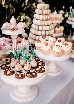 Kleurrijke candybar met snoep en gebak op houten stands