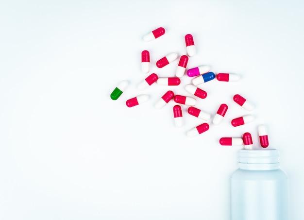 Kleurrijke capsulepillen die uit plastic drugfles worden uitgespreid. drugsgebruik met redelijk in het ziekenhuis.