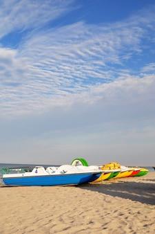 Kleurrijke catamarans dichtbij de overzeese kust op een verlaten strand bij dageraad