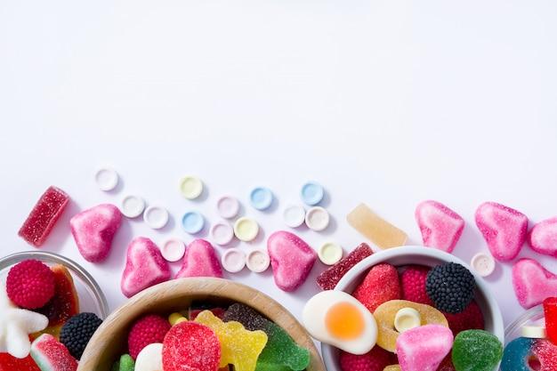 Kleurrijke childssnoepjes en traktaties in kom op wit