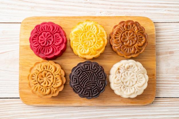 Kleurrijke chinese maancake met gemengde smaak op houten plaat