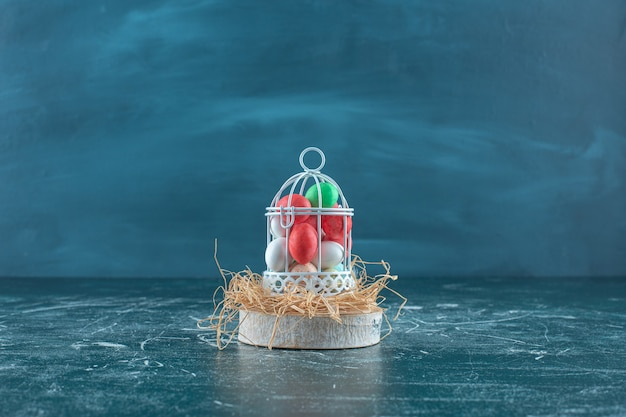 Kleurrijke chocolaatjes in een kooi op een droog rietje op het bord op het blauwe oppervlak