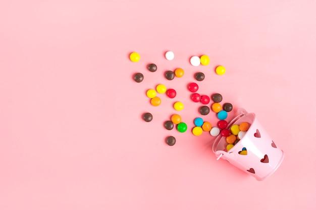 Kleurrijke chocolade snoepjes gemorst uit emmer met harten op een roze plat lag