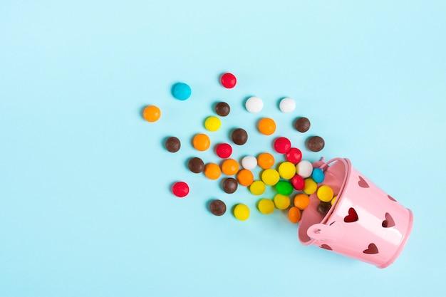 Kleurrijke chocoladesnoepjes gemorst uit emmer met hartjes op blauwe plat lag