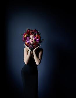 Kleurrijke cirkel gemaakt van verse bloemen op het gezicht van het mooie meisje, vrouw gekleed in zwarte strakke jurk op de donkerblauwe achtergrond