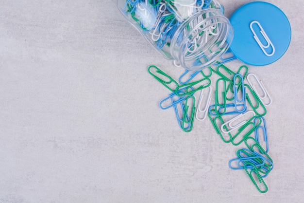 Kleurrijke clips in glazen pot op wit.