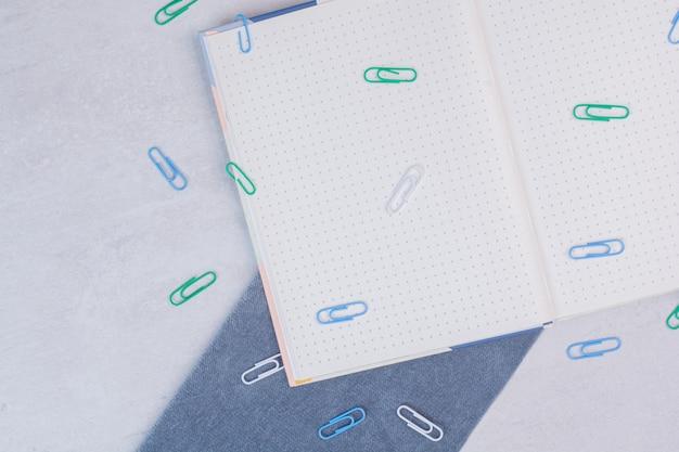 Kleurrijke clips verspreid over notebook op wit oppervlak
