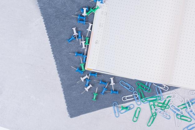 Kleurrijke clips verspreid over notebook op witte tafel.