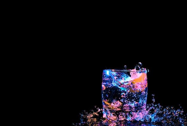 Kleurrijke cocktail in glas met spatten en citroen op donkere achtergrond. animatie van de partyclub. gemengd licht