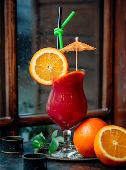 Kleurrijke cocktail met stukjes sinaasappel, cocktailparaplu, groen en zwart stro
