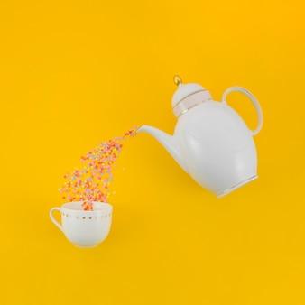 Kleurrijke confetti gieten van witte theepot in de keramische cup tegen gele achtergrond