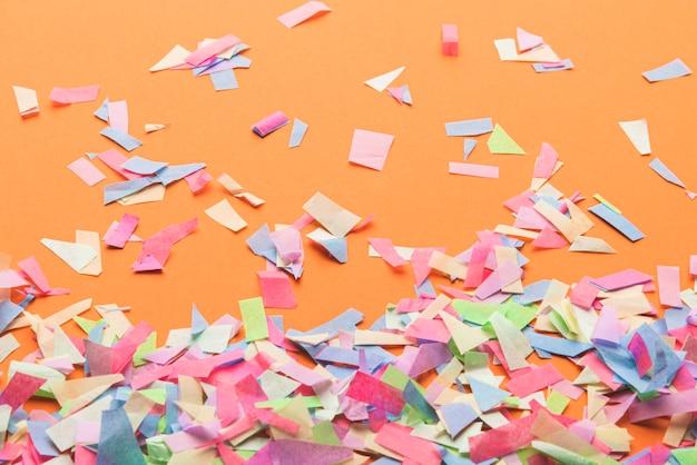 Kleurrijke confetti op oranje achtergrond