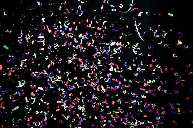 Kleurrijke confetti ruimte. rood, blauw, groen, geel op zwart. carnaval decoratie