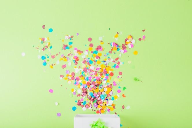 Kleurrijke confettien die in de witte doos over de groene achtergrond vallen