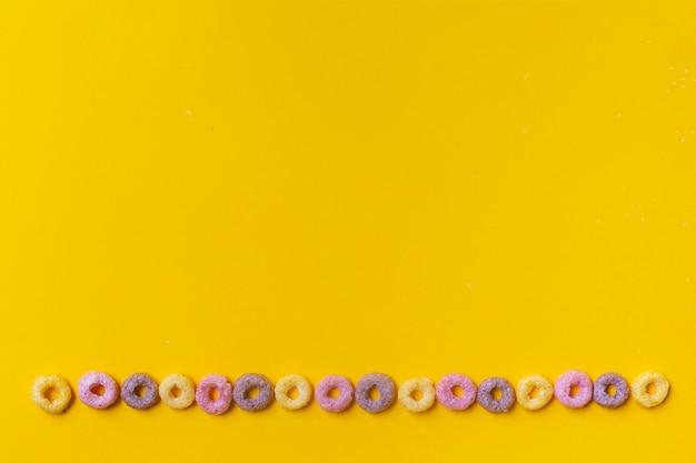Kleurrijke cornflakesringen op een gele achtergrond