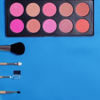 Kleurrijke cosmetica liggend op pastel achtergrond. make-up set. flatlay achtergrond voor ontwerp.