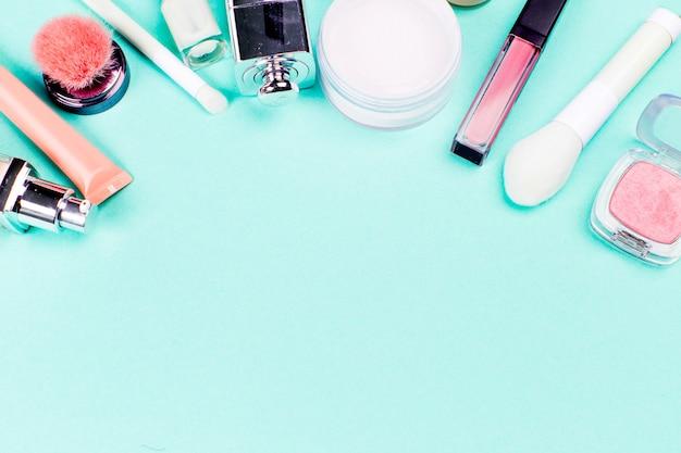 Kleurrijke cosmetica op blauwe werkplek. bovenaanzicht
