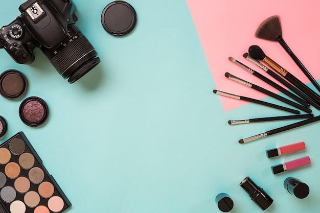 Kleurrijke cosmetica op blauwe werkplek met kopieerruimte cosmetica make-up artiest objecten lippenstift oog s...