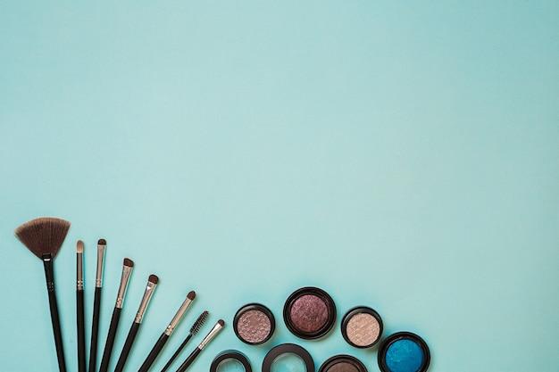 Kleurrijke cosmetica op blauwe werkplek met kopieerruimte cosmetica make-up artiest objecten oogschaduw om...