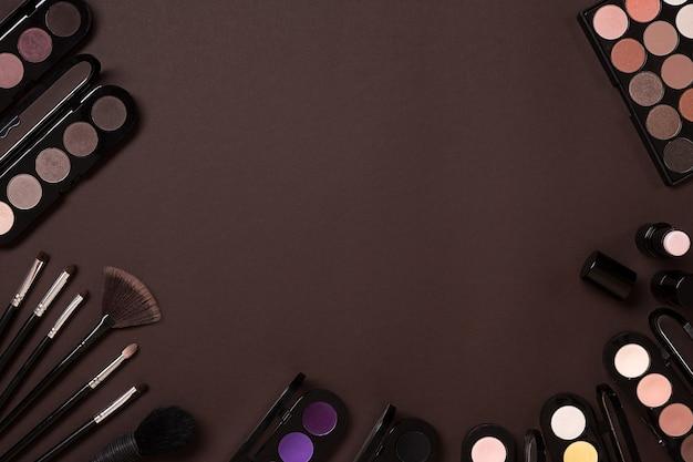Kleurrijke cosmetica op bruine werkplek met kopieerruimte cosmetica make-up artiest objecten lippenstift oog...