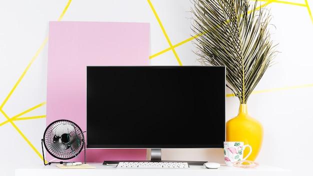 Kleurrijke creatieve werkplek met zwarte monitor