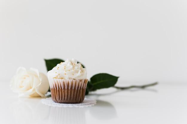 Kleurrijke cupcake op doily met roos tegen witte achtergrond