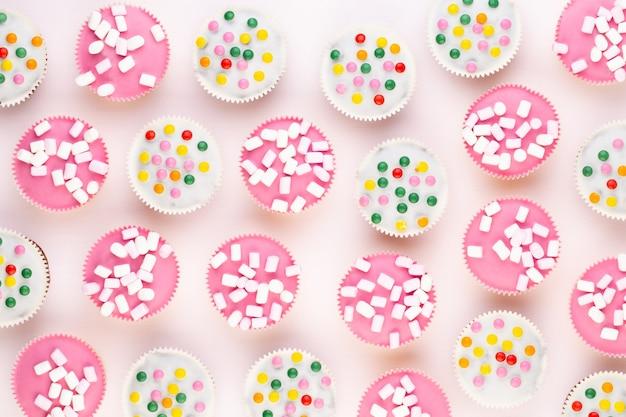 Kleurrijke cupcakes op een witte achtergrond.