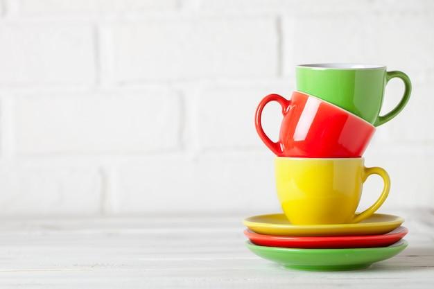 Kleurrijke cups op de witte achtergrond van een bakstenen muur. achtergrond met kopie ruimte. horizontaal. selectieve aandacht.