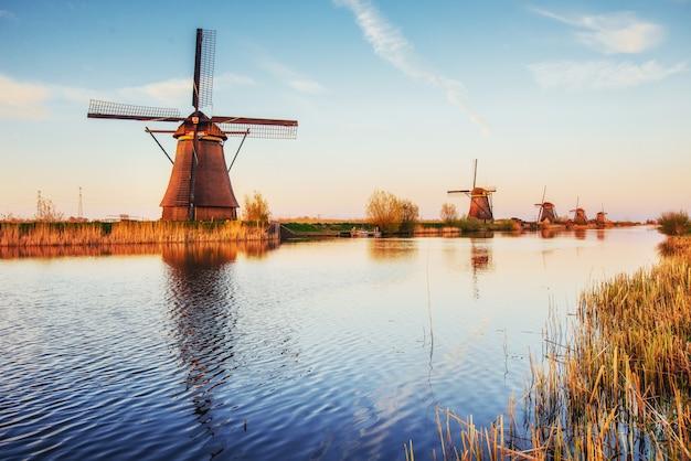 Kleurrijke de lentedag met traditioneel nederlands windmolenskanaal in rotterdam. houten pier in de buurt van de oever van het meer. holland.