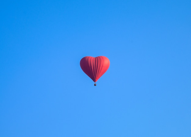 Kleurrijke de vormballons die van het hete luchthart in blauwe hemel vliegen